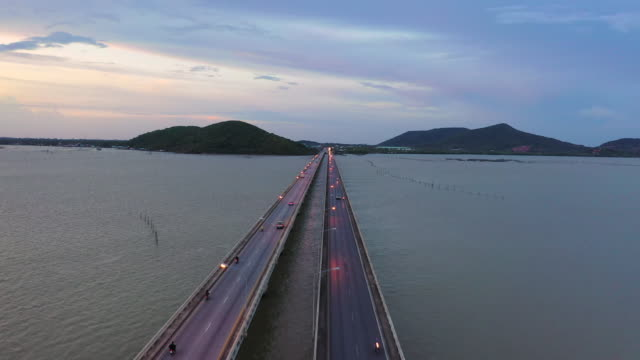 a directly above aerial drone shot of cars and vehicles driving along the bridge across lake, songkhla, thailand - coastal feature stock videos & royalty-free footage