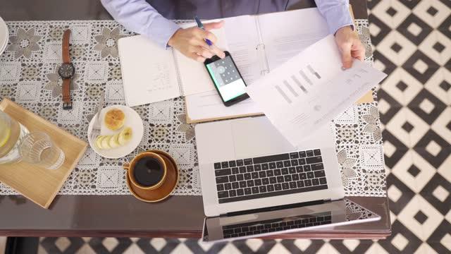 direttamente sopra asiatico cinese mid adulto uomo che frequenta la sua lezione online in cucina utilizzando laptop in t ha mattina - strategia di vendita video stock e b–roll