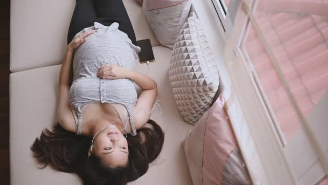 vidéos et rushes de directement au-dessus de la femme chinoise asiatique de grossesse se couchant sur le bâti de jour détendant appréciant la musique de son téléphone intelligent - chambre de bébé
