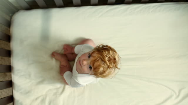 directly above caucasian baby boy with ruffled hair sitting in crib - one baby boy only stock videos & royalty-free footage