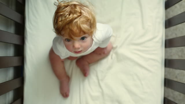 directly above caucasian baby boy with ruffled hair sitting in crib - babies only stock videos & royalty-free footage