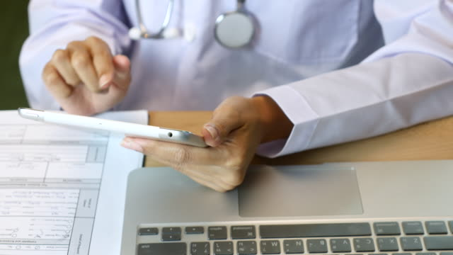 Directly Above Doctor's hands using digital tablet on wooden desk