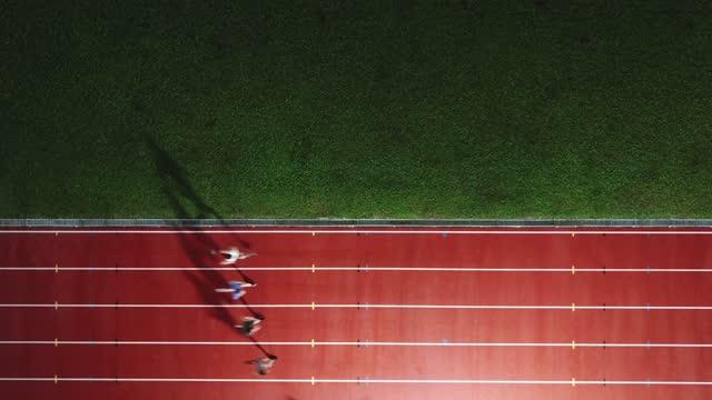vidéos et rushes de directement au-dessus du point de vue du drone athlète masculin chinois asiatique courant sur la piste masculine pluvieuse tard dans la soirée dans le stade - dessus