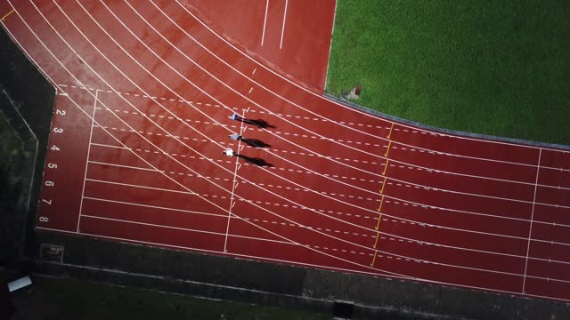 directly above drone point of view asian chinese male athlete running at men's track rainy late evening in stadium - sport venue stock videos & royalty-free footage
