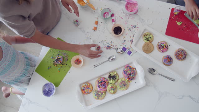 directly above, family decorating cookies together - decorating stock videos & royalty-free footage