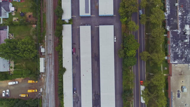vídeos de stock e filmes b-roll de directly above, looking-down top view of the industrial zone with self-storage hangars in long island, new york state, usa. aerial drone video with the slow panning camera motion. - hangar