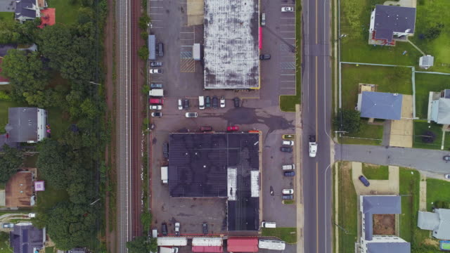 directly above, looking-down top view of the industrial zone with self-storage hangars in long island, new york state, usa. aerial drone video with the slow descending camera motion. - self storage video stock e b–roll