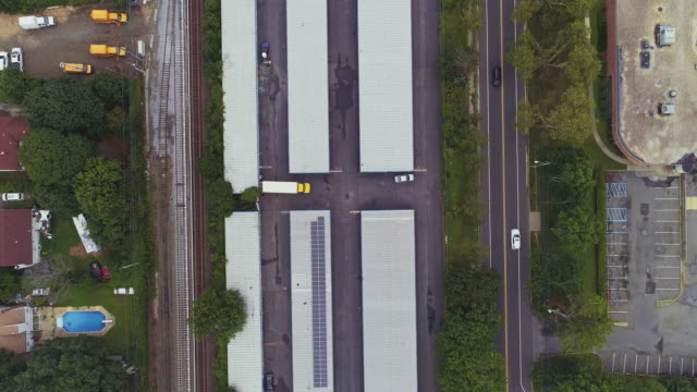 directly above, looking-down top view of the industrial zone with self-storage hangars in long island, new york state, usa. aerial drone video with the slow panning camera motion. - self storage video stock e b–roll