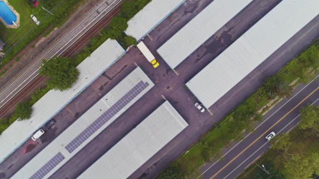 真上、ニューヨーク州ロングアイランドのセルフストレージ格納庫を備えた工業地帯のトップビュー。パンニングカメラの動きを持つ空中ドローンビデオ。 - トランクルーム点の映像素材/bロール