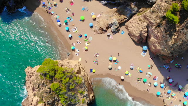 vídeos de stock e filmes b-roll de directly above of idyllic beach with people and island in the costa brava shoreline of spain. - tourist