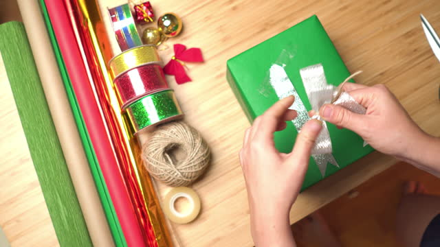 directly above, point of view: asian woman's hand attach the silver ribbon on a green gift with glue tape,  wrapping christmas presents from a brown paper box with green paper on the table at home at night. - christmas wrapping paper stock videos & royalty-free footage