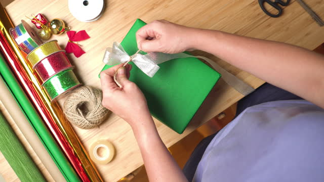 directly above, point of view: asian woman's hand preparing silver ribbon for adding the green gift,  wrapping christmas presents from a brown paper box with green paper on the table at home at night. - christmas wrapping paper stock videos & royalty-free footage
