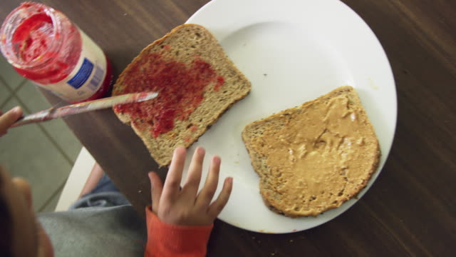 directly above shot of a cute six year-old caucasian boy using a kitchen knife to scoop jelly from the jar and then spreading it on to a piece of bread sitting on a plate while making a peanut butter and jelly sandwich at a kitchen table indoors - making a sandwich stock videos and b-roll footage