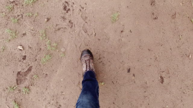 directly above shot of a person wearing jeans and hiking boots walking through mud and puddles of water outdoors - boot stock videos & royalty-free footage