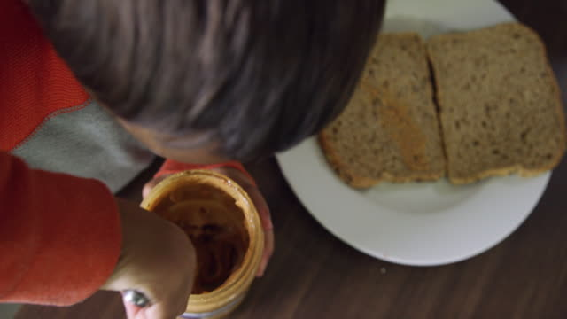 directly above shot of a six year-old caucasian boy's hands using a kitchen knife to scoop peanut butter out of a jar and spreading it on to a piece of bread on a plate while making a peanut butter and jelly sandwich at a kitchen table - making a sandwich stock videos and b-roll footage