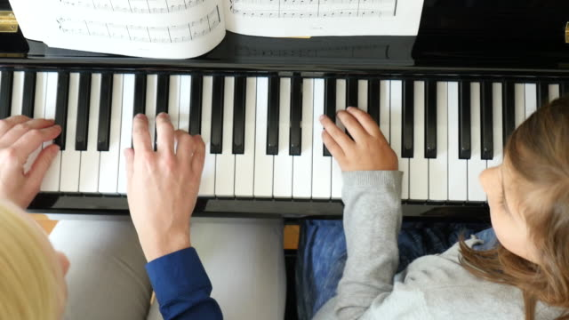 Directly above shot of mother teaching piano to daughter