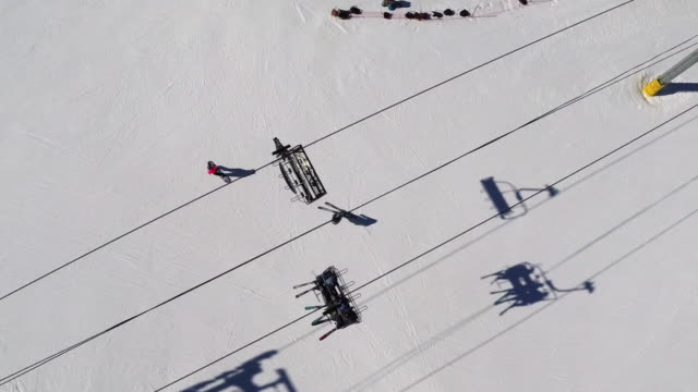 directly above shot of people skiing below ski lift - seggiovia video stock e b–roll