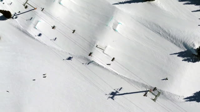 directly above shot of skiers riding chairlift at ski resort - seggiovia video stock e b–roll