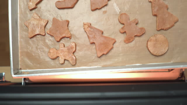 stockvideo's en b-roll-footage met directly above view: asian woman's hand opens door of the oven to preparing,  pushing fulfillment plate with baking homemade christmas cookies, tree star, gingerbread, sock, candy cane to hot air oven for a celebration of holiday's december. - star shape
