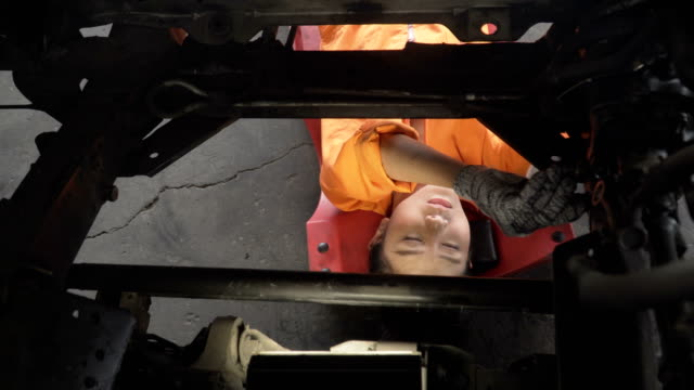 directly above view: asian young female car mechanic working from space of engine - sotto video stock e b–roll