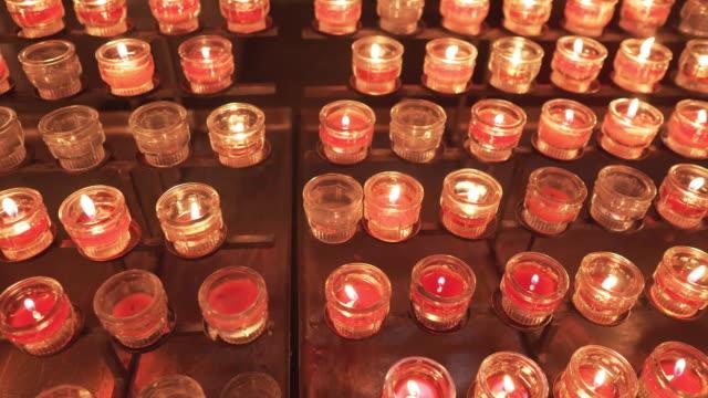 direttamente sopra la vista: maria e le candele, candele di preghiera rosse che bruciano di fila all'interno di una chiesa cattolica per pregare e spiritualità, cattedrale di salisburgo, la cattedrale barocca dell'arcidiocesi cattolica romana della città - bibbia video stock e b–roll
