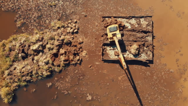vídeos de stock e filmes b-roll de directly above view of a digger in a swamp - terreno inóspito