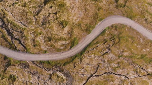 アイスランドの地殻の火山風景上の単一車線の泥道の真上の眺め - 散歩道点の映像素材/bロール