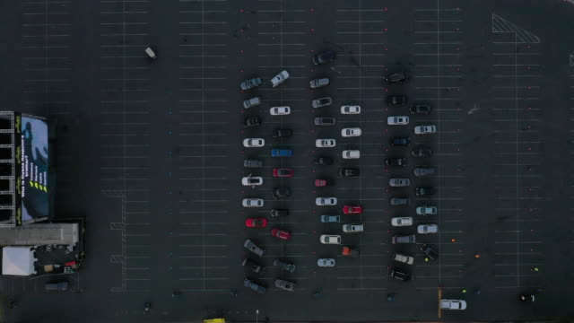 "directly above view of cars on parking lot during film screening. aerials of a drive-in movie screening of ""the new mutants"" in the parking lot of... - parking stock videos & royalty-free footage"