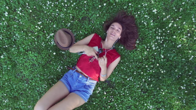 Directly above view of teenage girl resting in the grass
