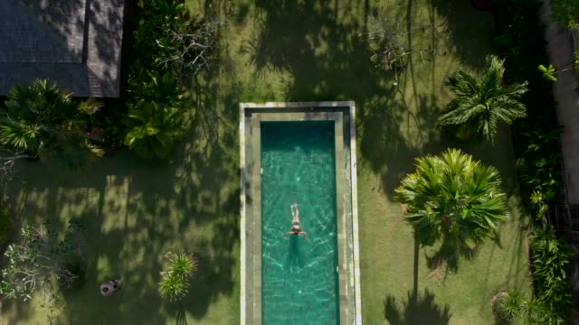vídeos de stock e filmes b-roll de directly above view of woman relaxing in swimming pool - bali