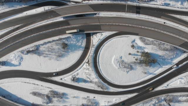 direkt über den blick auf die kreuzung autobahn ohne verkehr in der stadt der winter mit schnee bedeckt - straßenkreuzung stock-videos und b-roll-filmmaterial
