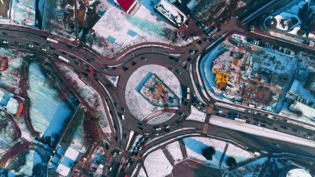 Directly above view on the roundabout with traffic in the winter city covered by snow