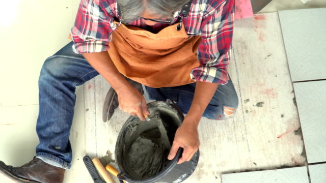 directly above view: senior man tiler mixing cement with trovel by himself - solo un uomo anziano video stock e b–roll