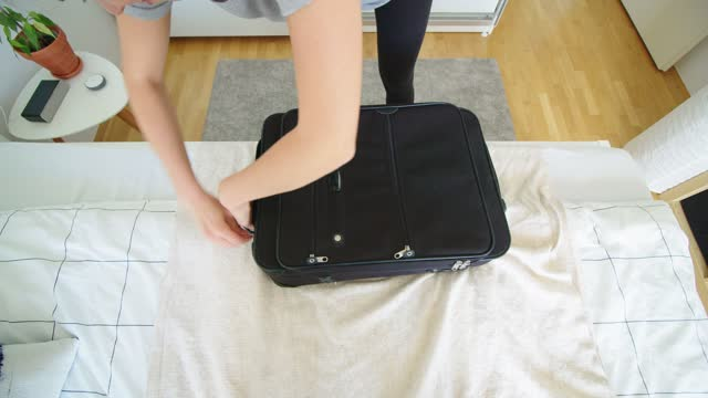 directly above - woman hands putting clothes in a suitcase - luggage stock videos & royalty-free footage