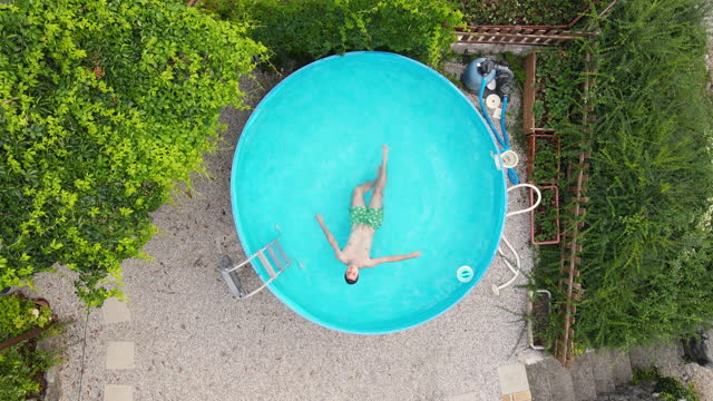directly above young man enjoying in swimming pool in backyard - reclining stock videos & royalty-free footage