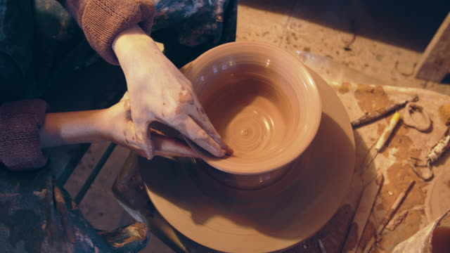 cu directly above, young woman working on a bowl in her ceramics studio - craft stock videos & royalty-free footage