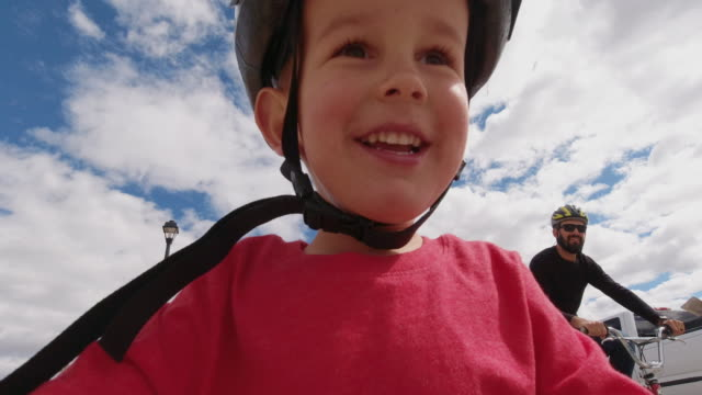 directly below shot of a four year-old caucasian boy wearing a bike helmet and smiling as he rides his bike with his thirty-something caucasian father under a partly cloudy sky - helmet stock videos & royalty-free footage