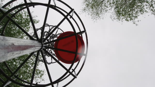 directly below shot of an orange disc golf putter hitting the chains of a disc golf basket (goal) at a disc golf course (frisbee golf) - holing stock videos & royalty-free footage