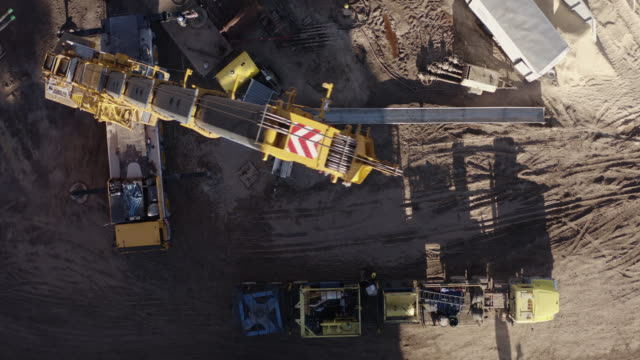 directly overhead aerial drone shot of a crane breaking down a rig at an oil and gas drilling pad site in a valley on a sunny day - oil industry stock videos & royalty-free footage