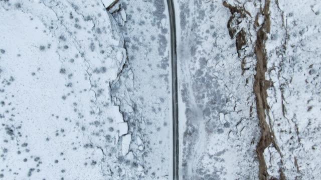 Direkt Overhead Aerial Drone Schuss einer verschneiten Straße schlängelt sich durch eine felsige Wüste Schlucht im Winter