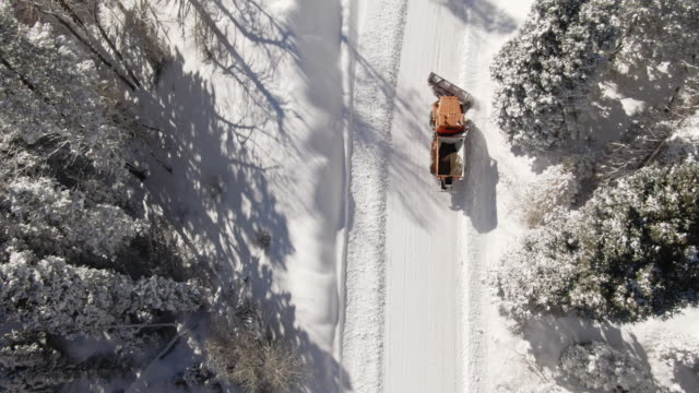 directly overhead aerial drone shot of an orange tractor plowing deep snow in a forest in the mountains in winter under a bright, sunny sky - snowplough stock videos & royalty-free footage