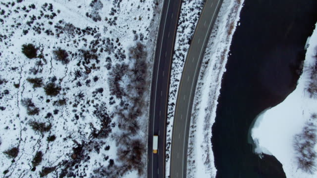 directly overhead aerial drone shot of cars and vehicles driving on interstate 70 in the rocky mountains of colorado next to the colorado river on a snowy, winter day - colorado stock videos & royalty-free footage