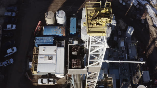directly overhead aerial drone shot of the top of a derrick at an oil and gas drilling pad site on a sunny day - oil industry stock videos & royalty-free footage