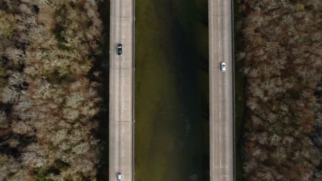 directly overhead ascending aerial drone shot of breaux bridge (interstate 10) and the atchafalaya river basin swamp surrounded by cypress tree forests in southern louisiana on a sunny day - louisiana stock videos & royalty-free footage