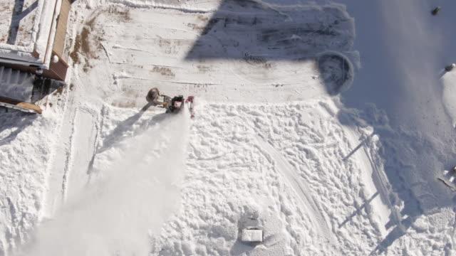 明るい冬の日の雪に覆われた家の前で吹いて男雪の真上の降順空中ドローン ショット - ユアレイ市点の映像素材/bロール
