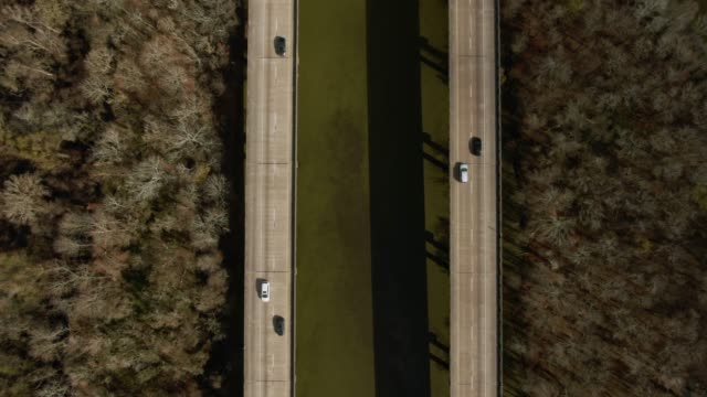 directly overhead descending aerial drone shot of breaux bridge (interstate 10) and the atchafalaya river basin swamp surrounded by cypress tree forests in southern louisiana on a sunny day - interstate 10 stock videos & royalty-free footage