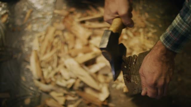 vídeos y material grabado en eventos de stock de disparo directo de las manos de un hombre cortando leña de un tronco con un hacha en un taller - work tool