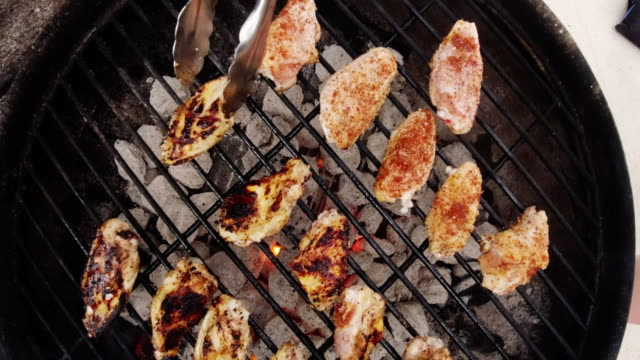 directly overhead shot of a pair of metal tongs flipping over chicken wings cooking on an outdoor barbecue on a metal grate with lit charcoal briquettes underneath - pollo alla brace video stock e b–roll