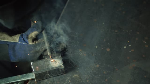 directly overhead shot of a person mig welding on a metal welding table in a workshop as sparks fly - welding helmet stock videos & royalty-free footage
