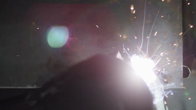 direkt über kopf schießen von einer person mig schweißen auf einem metallschweißtisch in einem workshop als sparks fly - handwerker stock-videos und b-roll-filmmaterial